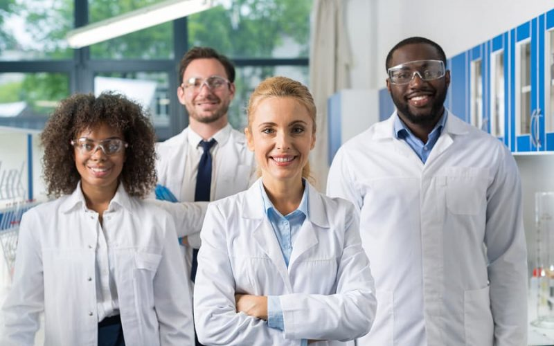 Smiling Group Of Scientists In Modern Laboratory With Female Leader, Mix Race Team Of Scientific Researchers In Lab Wearing White Coats And Protective Glasses